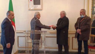 Photo of Au nom du Président de la République ,L'ambassadeur d'Algérie en France remet l'emblème national à la famille d'Ali Boumendjel